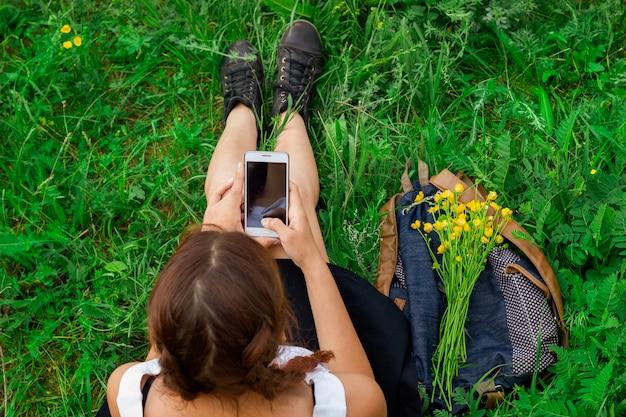 Mulher, sentando, ligado, grama verde, com, telefone, em, mão, vista superior