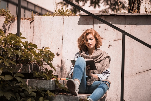 Mulher, sentando, ligado, passos, e, livro leitura