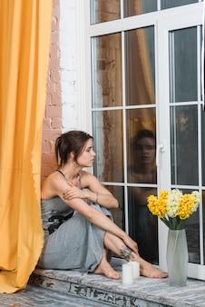 Mulher, sentando, ligado, peitoril janela
