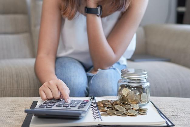 Mulher, sentando, ligado, sofá, usando, calculadora, com, moeda ouro, e, garrafa copo
