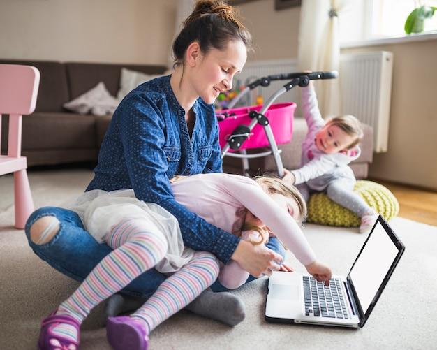 Mulher, sentando, ligado, tapete, olhar, menina, usando computador portátil