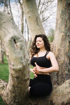 Mulher, sentando, ligado, tronco árvore, meditar, com, mudra, gesto
