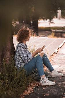 Mulher, sentando, perto, árvore, e, segurando, livros