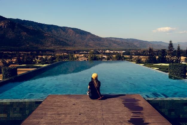 Mulher, sentando, por, poolside, com, vista montanha
