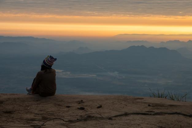 Mulher, sentando, serenely, de, a, penhasco, e, olhar, a, vale, e, montanhas, de manhã