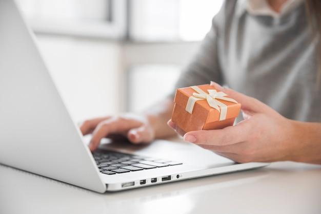 Mulher, sentando tabela, com, laptop, e, caixa presente