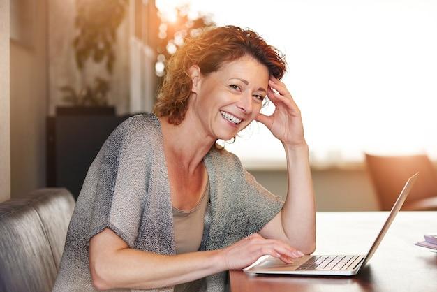 Mulher, sentando tabela, com, sorrindo, com, laptop