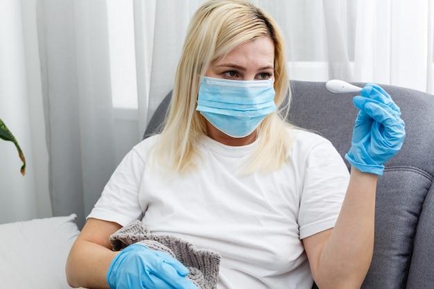 Mulher sente frio e enjoos com o vírus corona. ele usa um termômetro para verificar a temperatura corporal
