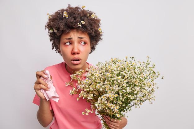 Mulher sente-se mal, sofre de sintomas de alergia segura tecido na mão alérgica a flores silvestres segura buquê de poses de camomila no branco