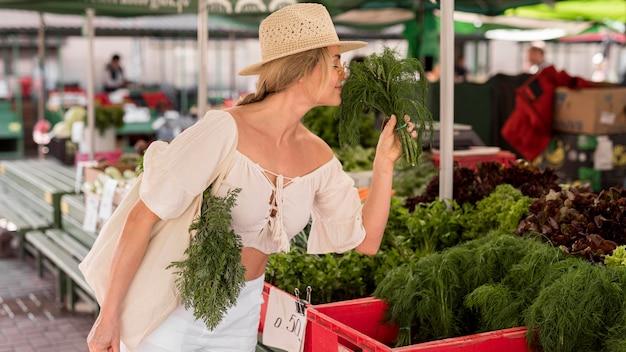 Mulher sentindo o cheiro de endro do mercado