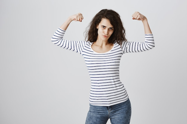Mulher sentindo-se fortalecida flexionando bíceps após o treino