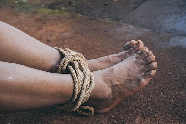 Mulher sequestrada amarrada com corda - conceito de abuso e violência