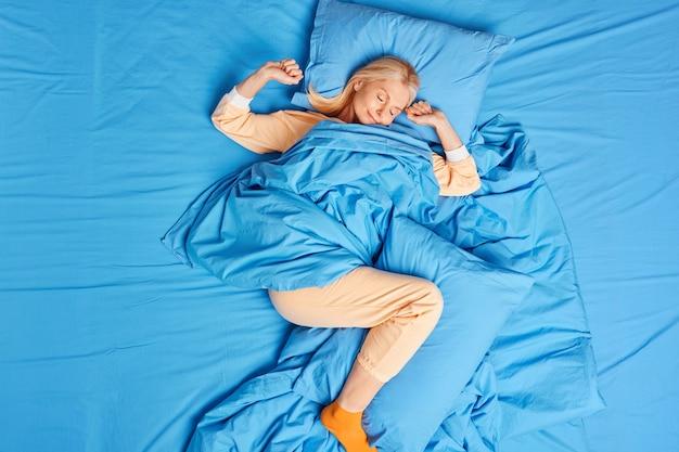 Mulher serena de meia-idade, deitada confortável na cama, usa um pijama confortável, estende os braços, vê sonhos agradáveis, dorme bem sozinha, desfruta de uma boa noite de sono tranquilo e saudável. conceito de sono e conforto