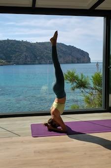 Mulher serena fazendo ioga em pose de apoio para a cabeça