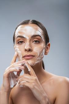 Mulher serena limpando o rosto com espuma