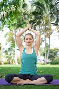 Mulher serena sentada em posição de ioga ao ar livre