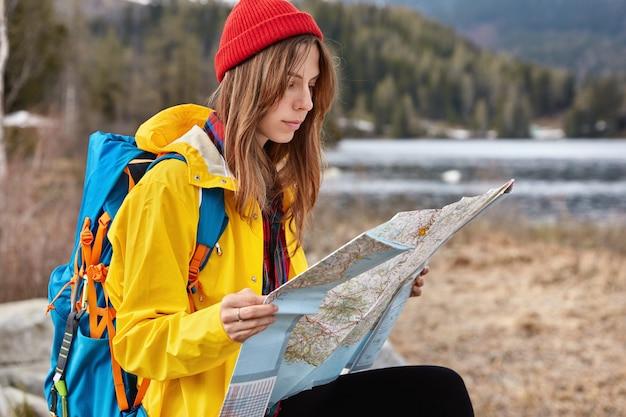 Mulher séria, andarilho sentado e estudando o mapa com atenção