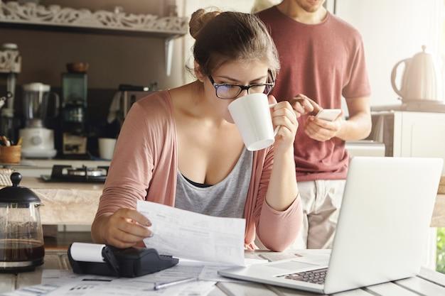 Mulher séria atraente em espetáculos, bebendo café e estudando o documento nas mãos dela, gerenciando o orçamento familiar e fazendo a papelada na mesa da cozinha com uma pilha de contas, laptop e calculadora