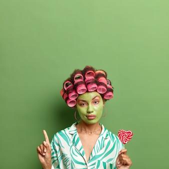 Mulher séria autoconfiante aplica rolos de cabelo segura pirulito saboroso faz tratamentos faciais de beleza vestida em poses de pijama contra a parede verde aponta para cima. cuidados com a pele e penteado
