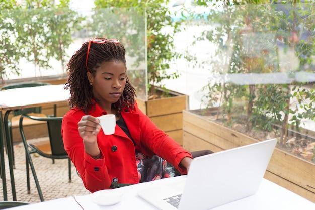 Mulher séria, bebendo café e usando o laptop