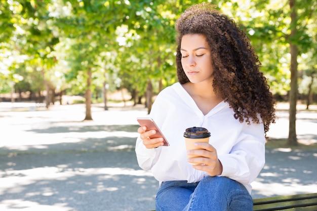 Mulher séria, bebendo café e usando smartphone no banco