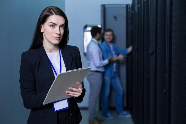 Mulher séria, bonita e simpática parada no meio da sala do servidor, segurando anotações enquanto verifica o trabalho dos técnicos