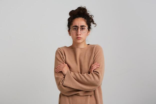 Mulher séria, carrancuda, com um coque de cabelo encaracolado escuro, vestindo um macacão bege e óculos