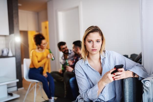 Mulher séria caucasiana atraente usando telefone inteligente enquanto seus amigos conversando e bebendo. sala interior.