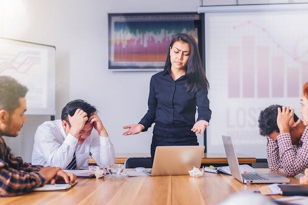 Mulher séria chefe repreendendo empregado de equipe de marketing para resultados de má negócios em reunião