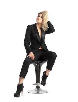 Mulher séria com cabelo loiro encaracolado se senta na cadeira em um terno de negócios preto sobre fundo branco