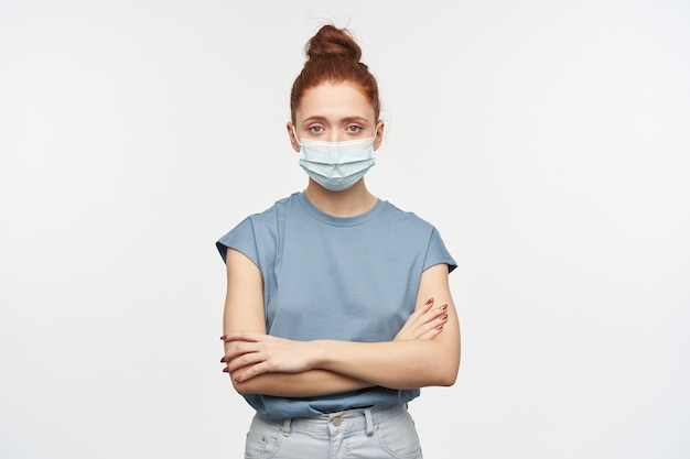 Mulher séria com cabelo ruivo preso em um coque. vestindo camiseta azul, jeans e máscara protetora. mãos cruzadas em um baú. isolado sobre a parede branca