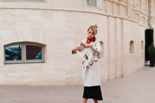 Mulher séria com casaco longo bege caminhando pelo prédio e lendo notícias recentes
