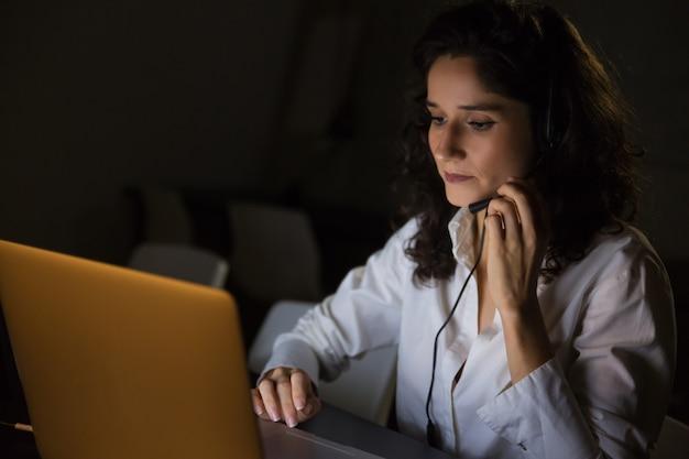Mulher séria com fone de ouvido usando laptop