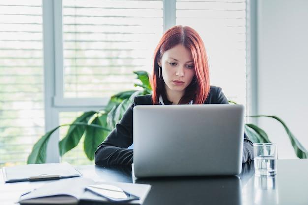 Mulher séria com laptop no escritório