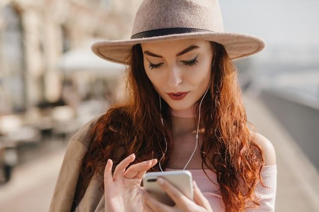Mulher séria com longos cabelos escuros olhando para a tela do telefone