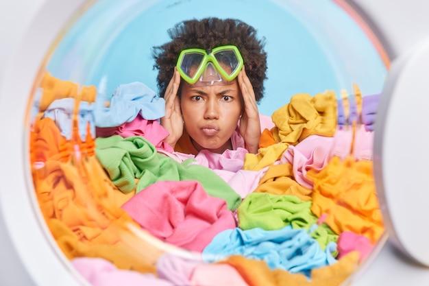 Mulher séria com máscara de mergulho na testa mantém os lábios dobrados e olha com raiva em poses frontais com roupas multicoloridas desdobradas na visão da máquina de lavar