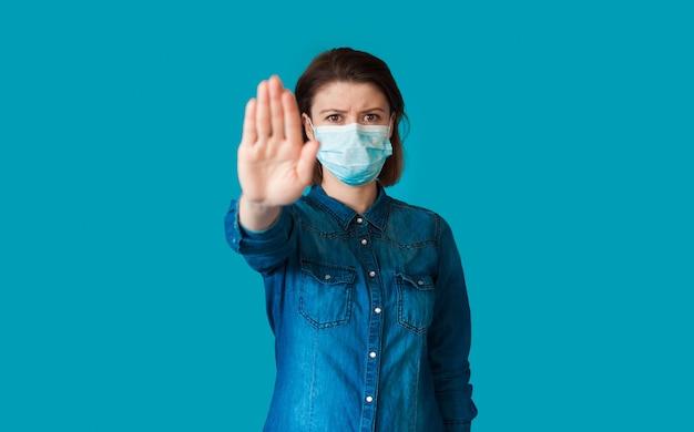 Mulher séria com máscara médica no rosto gesticulando uma placa de pare com a palma da mão posando na parede azul do estúdio