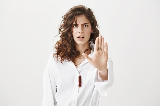 Mulher séria com raiva mostrando gesto de parar, discordar e proibir ação