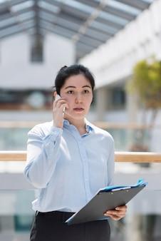 Mulher séria com tiro médio no telefone