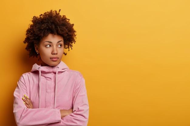 Mulher séria de cabelos cacheados determinada fica pensativa, pondera sobre algo, olha para o lado, mantém os braços cruzados, considera uma decisão importante, isolada na parede amarela, espaço vazio à parte.