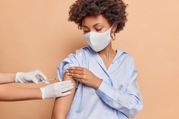 Mulher séria de cabelos cacheados usa máscara protetora contra vírus usa camisa azul e recebe inoculação no ombro isolado na parede bege