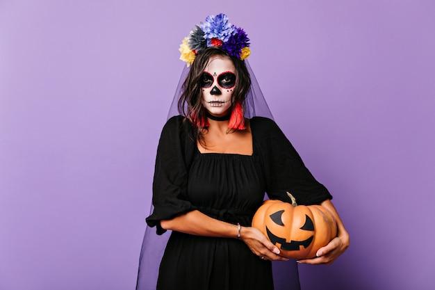 Mulher séria de cabelos castanhos com véu segurando abóbora de halloween. foto interna da linda garota com roupa de noiva morta com maquiagem assustadora.