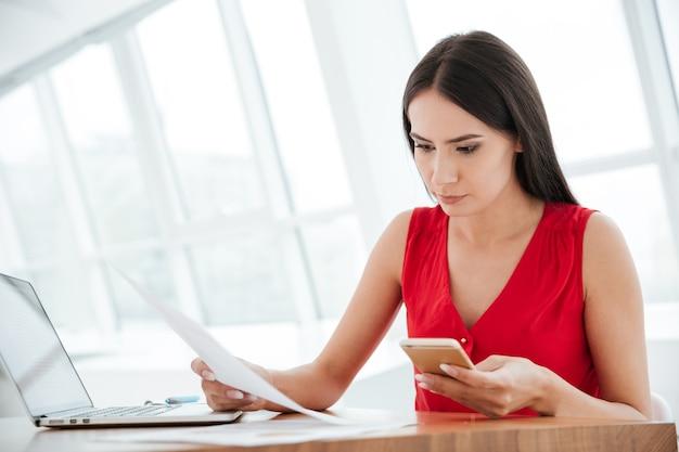 Mulher séria de camisa vermelha sentada à mesa com laptop, telefone e documentos no escritório