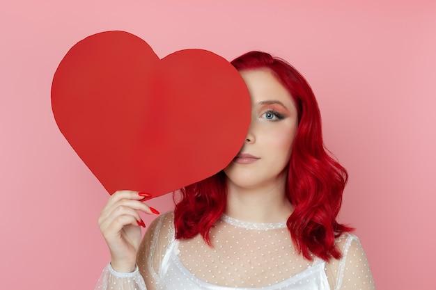 Mulher séria de close-up com cabelo ruivo escondendo metade do rosto atrás de um grande coração vermelho de papel