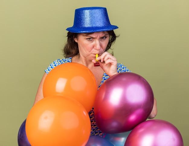 Mulher séria de meia-idade com chapéu de festa com um monte de balões coloridos, soprando um apito com o rosto carrancudo