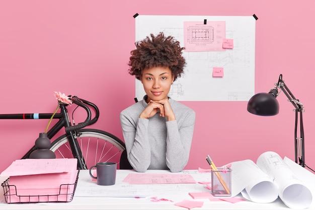 Mulher séria, de pele escura, prepara projeto de construção ou poses de designer de interiores na área de trabalho com projetos de papel no escritório