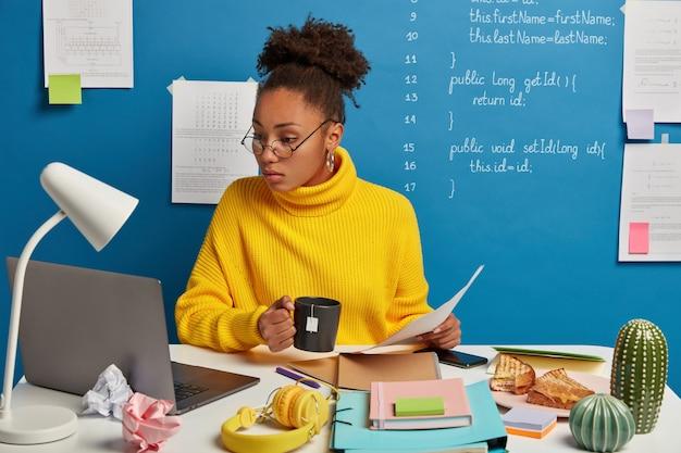 Mulher séria de pele escura verifica informações em jornais e laptop, assiste a um webinar de treinamento sobre programação de computador