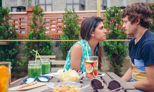 Mulher séria discutindo com o jovem sentado atrás da mesa com bebidas e lanches saudáveis em um dia de verão ao ar livre