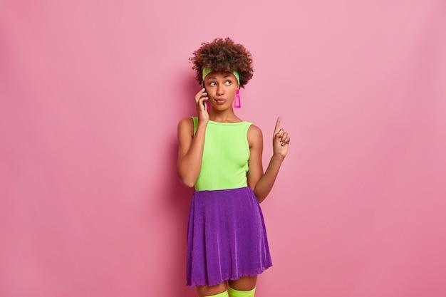 Mulher séria e atenciosa de pele escura na moda fala via celular, aponta o dedo indicador para cima e usa roupas brilhantes