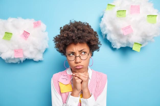 Mulher séria e atenciosa faz anotações em adesivos para memorizar, mantém as mãos embaixo do queixo e usa óculos desgastados, roupas elegantes isoladas sobre a parede azul